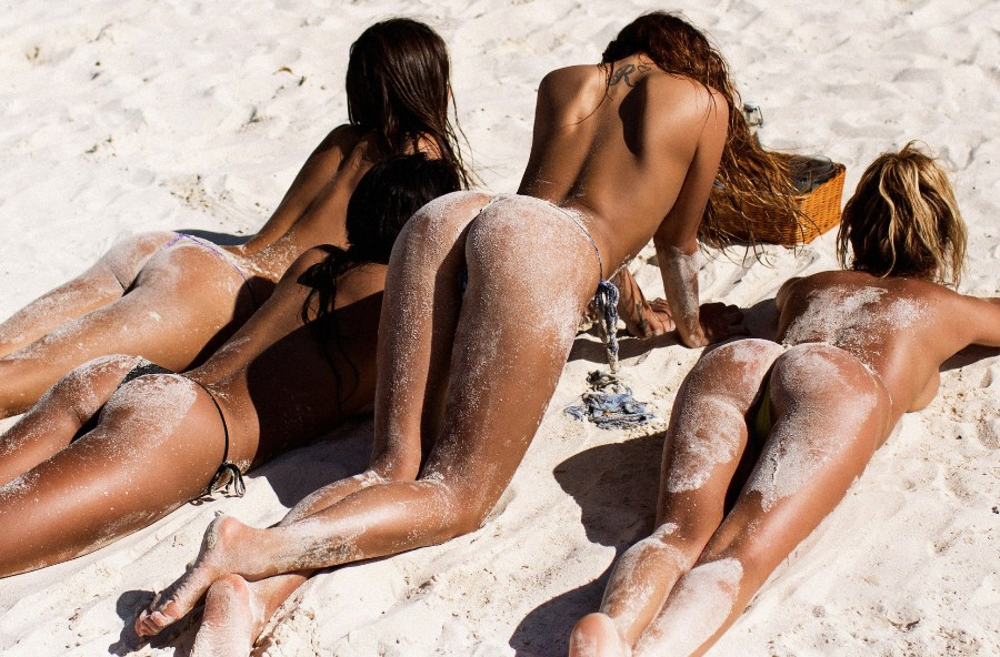 Четыре загорелые девушки на пляже